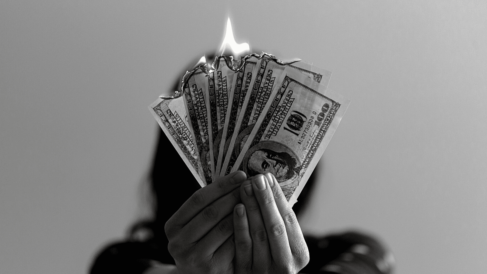 Dollar bills on fire being held by a person