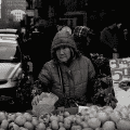 Person selling fruit at a market (black and white)