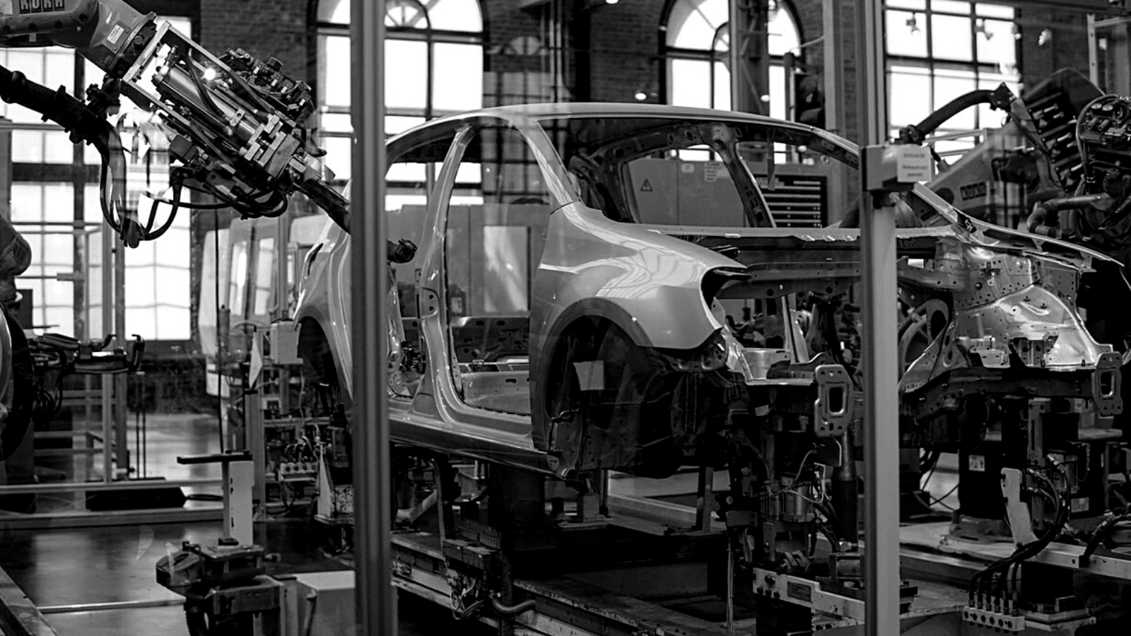 Black and white image of a car being built in a factory